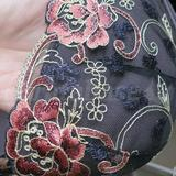 The embroidered flowers feature metallic embroidery.